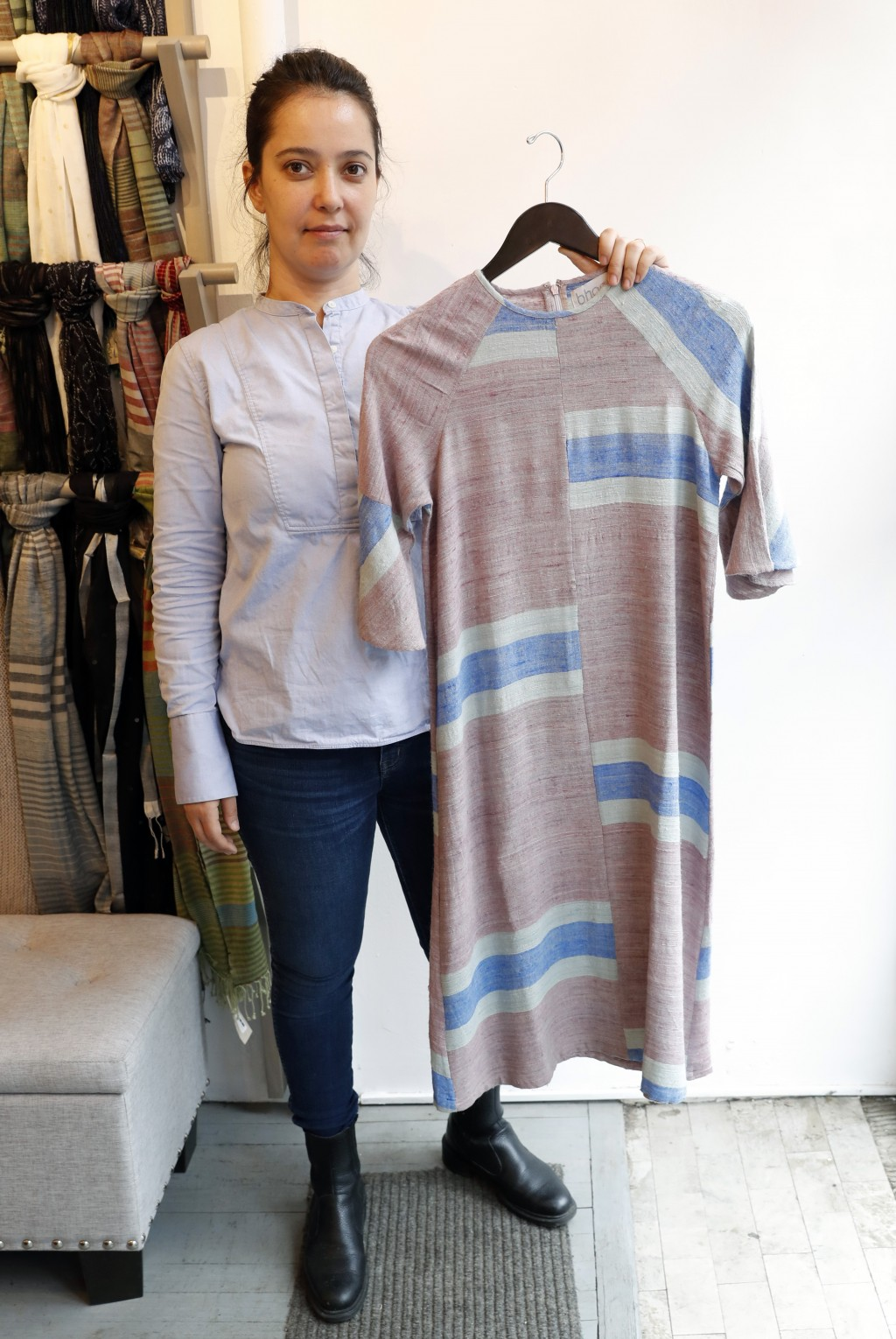 """Amanda Jimenez holds a """"peace vegan silk"""" midi-dress at Bhoomki, a Brooklyn store specializing in """"ethically-fashioned"""" and hand-crafted clothing and"""