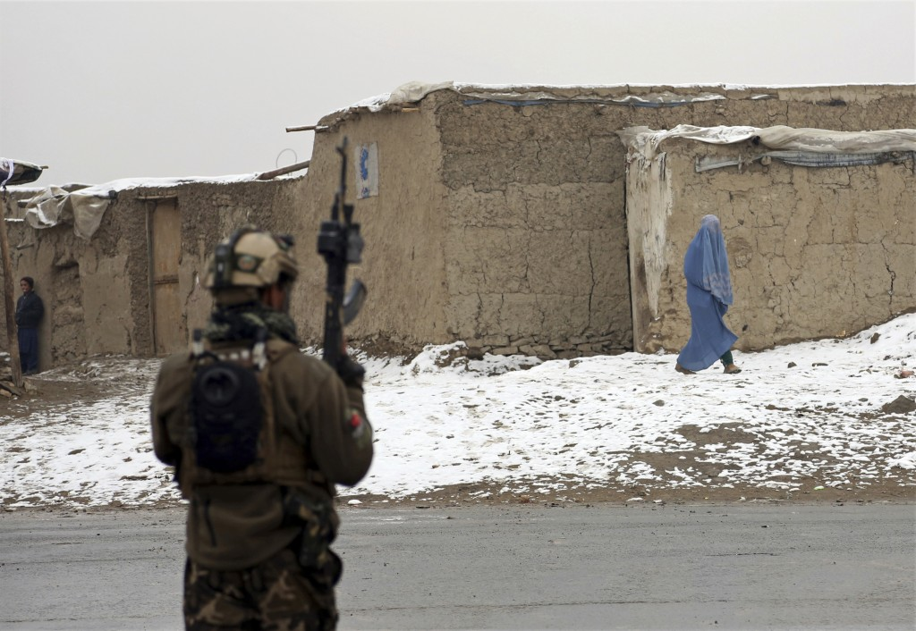An Afghan woman leaves the site of an attack at the Marshal Fahim academy in Kabul, Afghanistan Monday, Jan. 29, 2018. Islamic State militants attacke...