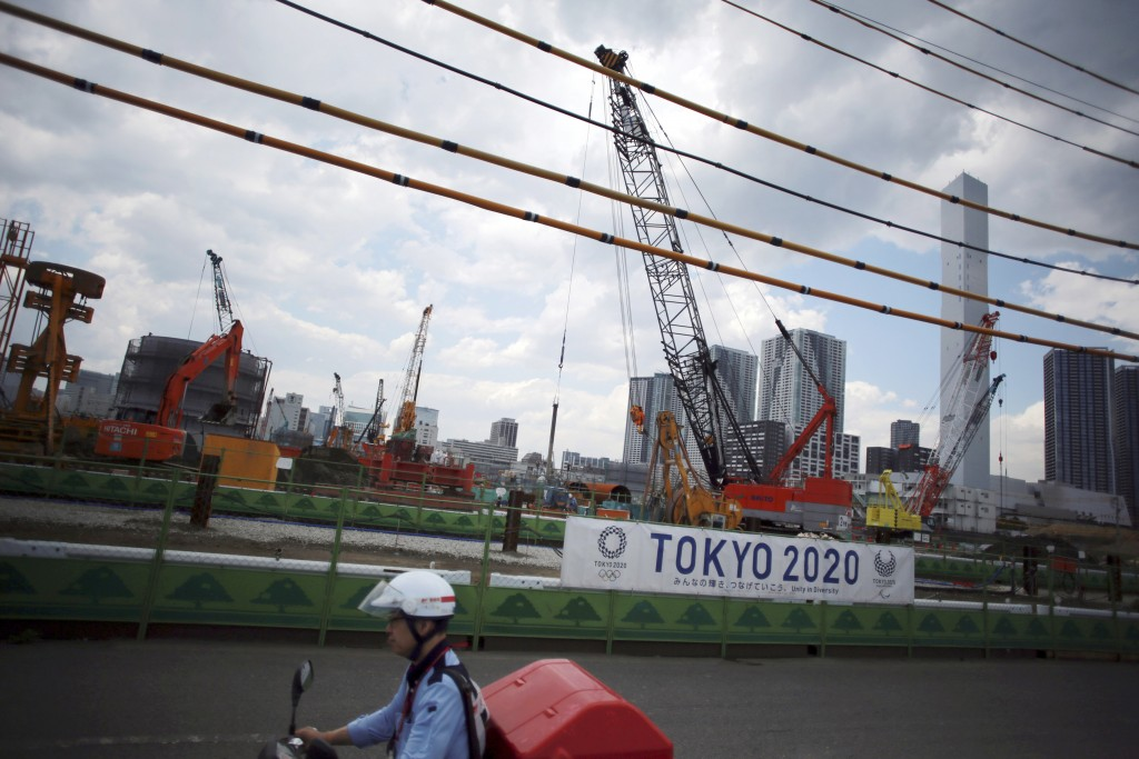 FILE - In this June 2, 2017, file photo, a postman rides a motorcycle past the construction site of the athlete's village for the 2020 Tokyo Summer Ol...