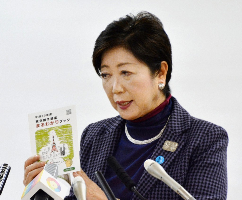 In this Friday, Jan. 26, 2018 photo, Tokyo Gov. Yuriko Koike holds a brochures of a 2018 draft budget while speaking during a press conference in Toky...
