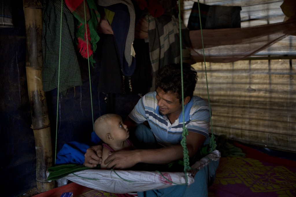 In this Jan. 21, 2018 photo, Rohingya Muslim refugee Noor Kadir, 24, from the Myanmar village of Gu Dar Pyin, plays with his son inside the family mak