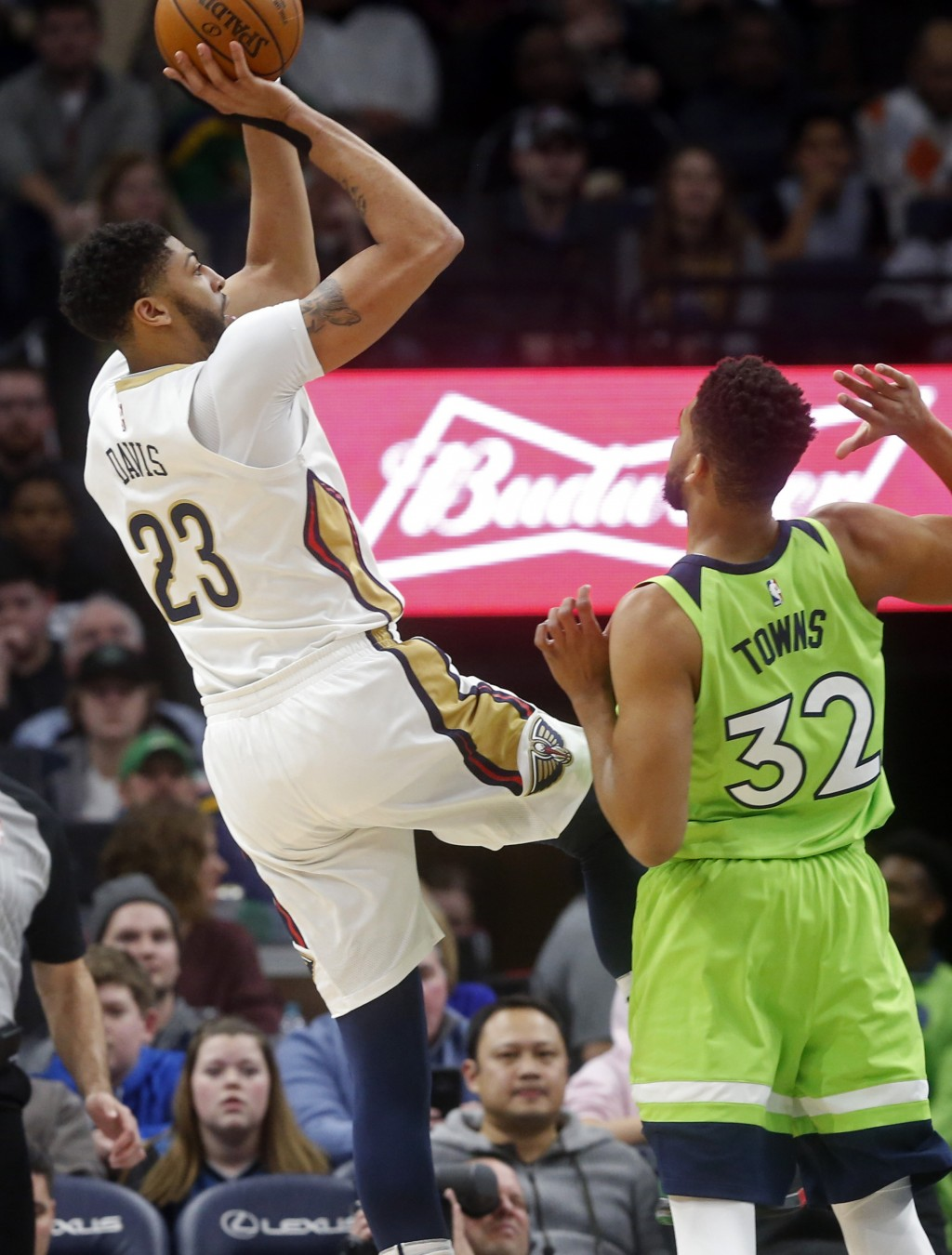 New Orleans Pelicans' Anthony Davis, left, shoots as Minnesota Timberwolves' Karl-Anthony Towns looks on in the first half of an NBA basketball game S...