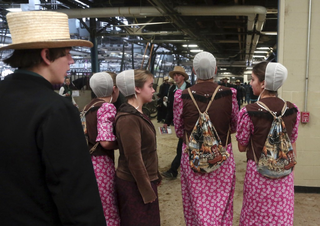 Teenage girls walk around the Pennsylvania Farm Show Complex during a horse auction Wednesday Jan.17, 2018 in Harrisburg, Pa. Amish from all over the