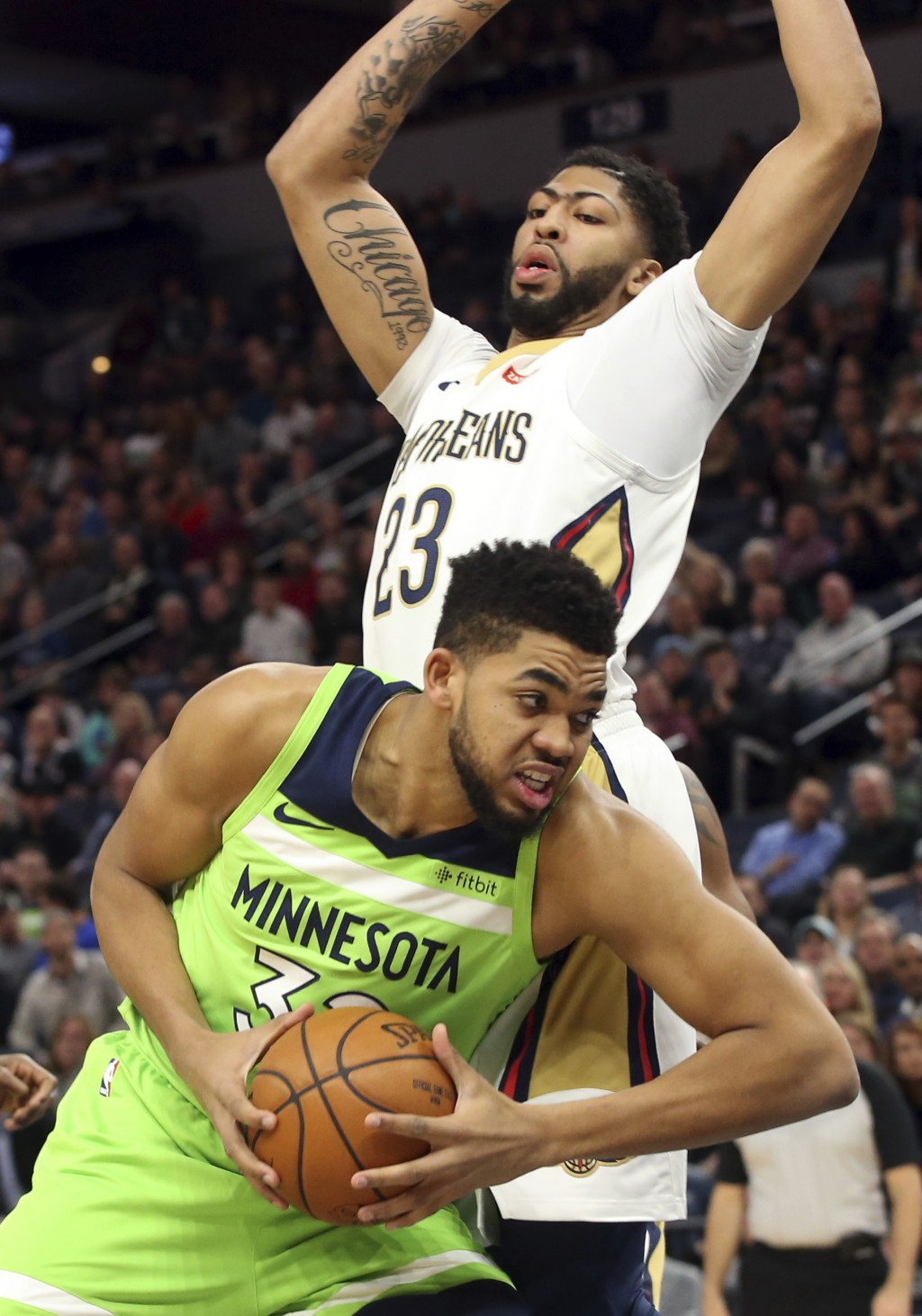 Minnesota Timberwolves' Karl-Anthony Towns, bottom, drives around New Orleans Pelicans' Anthony Davis, top, in the first half of an NBA basketball gam...