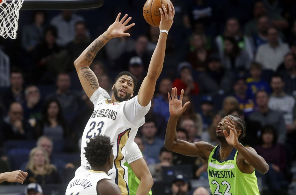 New Orleans Pelicans' Anthony Davis, left, beats Minnesota Timberwolves' Andrew Wiggins to a rebound in the first half of an NBA basketball game Satur...
