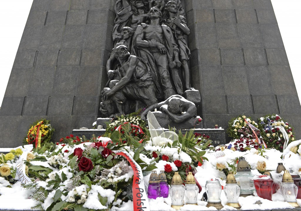 Snow covers flowers at the Warsaw Ghetto Uprising memorial in Warsaw, Poland, Tuesday, Feb. 6, 2018. Poland's president Andrzej Duda said Tuesday he w