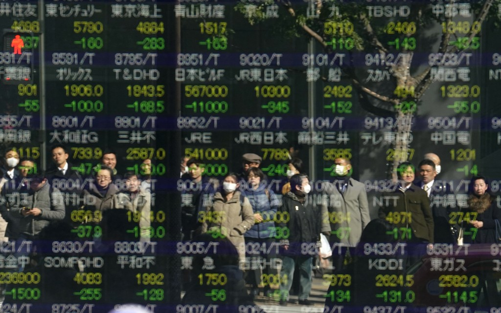 People are reflected on an electronic stock indicator of a securities firm in Tokyo Tuesday Feb. 6 2018. Shares tumbled in Asia on Tuesday after