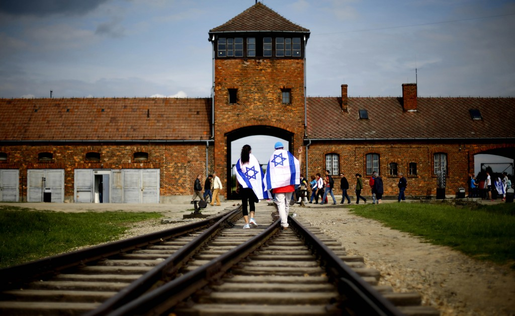 FILE- This June 25, 2015 file picture shows Brzezinka or Birkenau nazi death camp near Oswieciem, Poland, when young visitors with Israeli flags walk