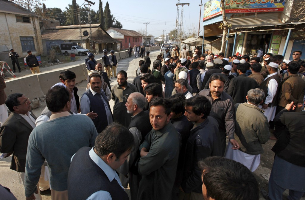 Family members and relatives of suspects in a case regarding the lynching of 23-year-old university student Mohammad Mashal Khan gather outside a cent