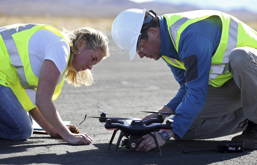 Jessica Balik, left, and Keven Gambold, right, CEO of Unmanned Experts, prepare a drone for a demonstration at the Searchlight airport in Searchlight,...