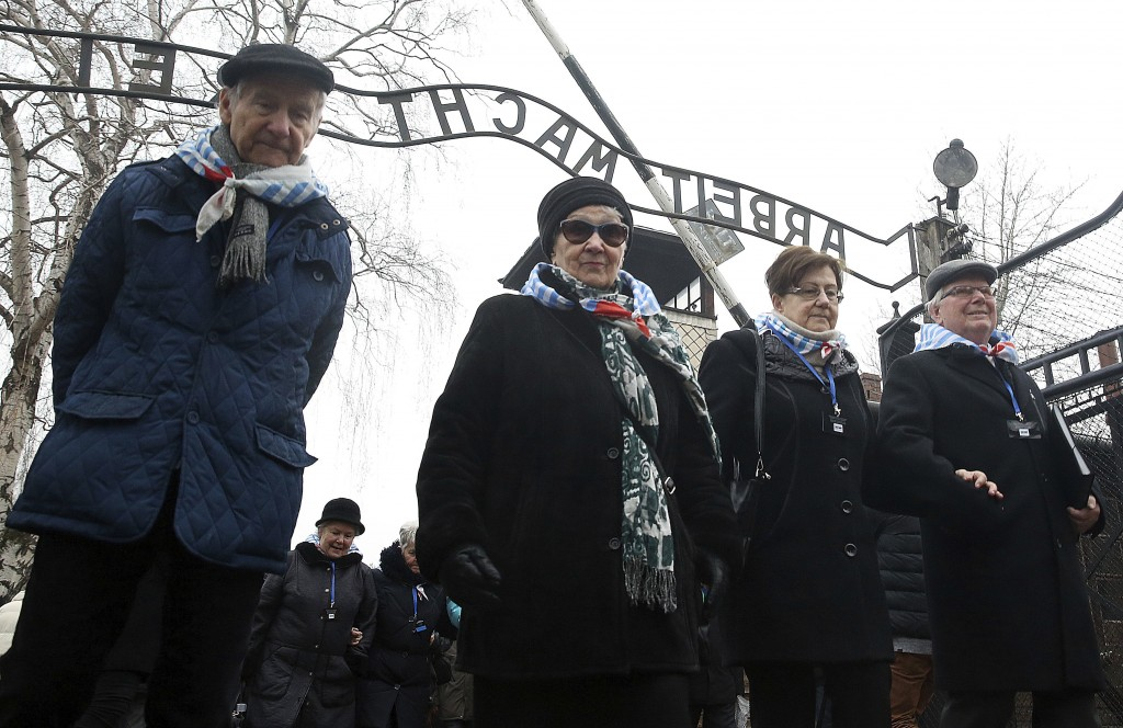 "FILE - In this Saturday, Jan. 27, 2018 file photo, survivors and guests walk past the ""Arbeit Macht Frei"" gate at the former Nazi German concentration"