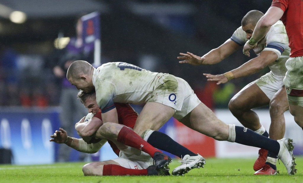England's Mike Brown, top, pushes Wales' Gareth Anscombe into touch during the Six Nations international rugby union match at Twickenham stadium in Lo