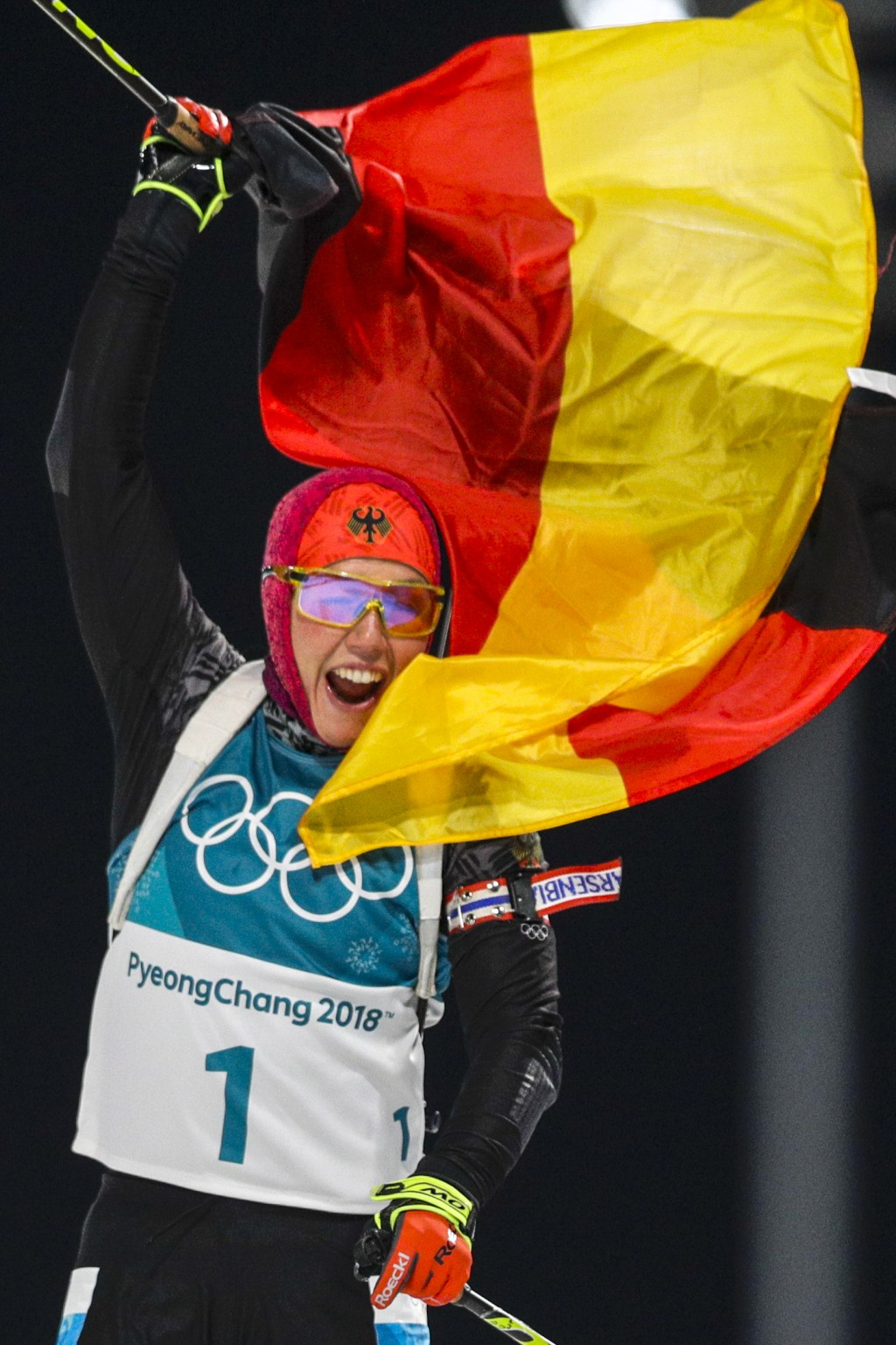 Laura Dahlmeier, of Germany, waves the German flag as she wins the gold medal in the women's 10-kilometer biathlon pursuit at the 2018 Winter Olympics