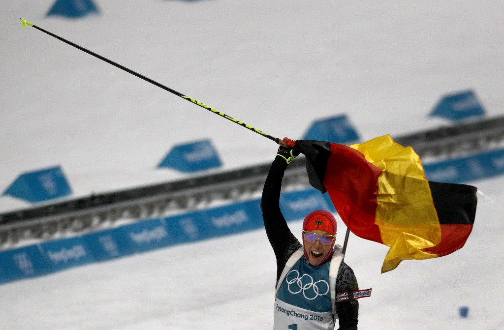 Laura Dahlmeier, of Germany, waves the German flag as she crosses the finish line to win the gold medal in the women's 10-kilometer biathlon pursuit a