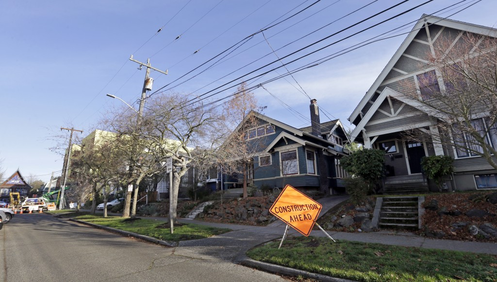 In this Dec. 13, 2017, photo, a four-story mixed-use building is under construction at the end of a street of older, single-family homes in Seattle. A...