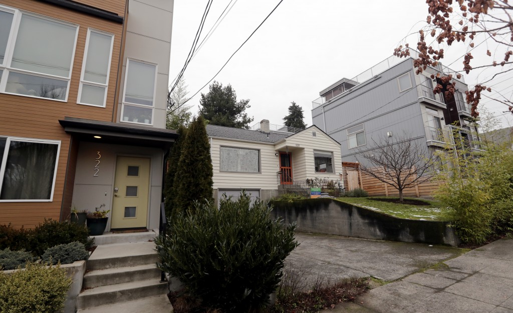 In this Dec. 27, 2017, photo, an older single-family home remains boxed-in between newer, multi-family homes in Seattle. A massive influx of new resid