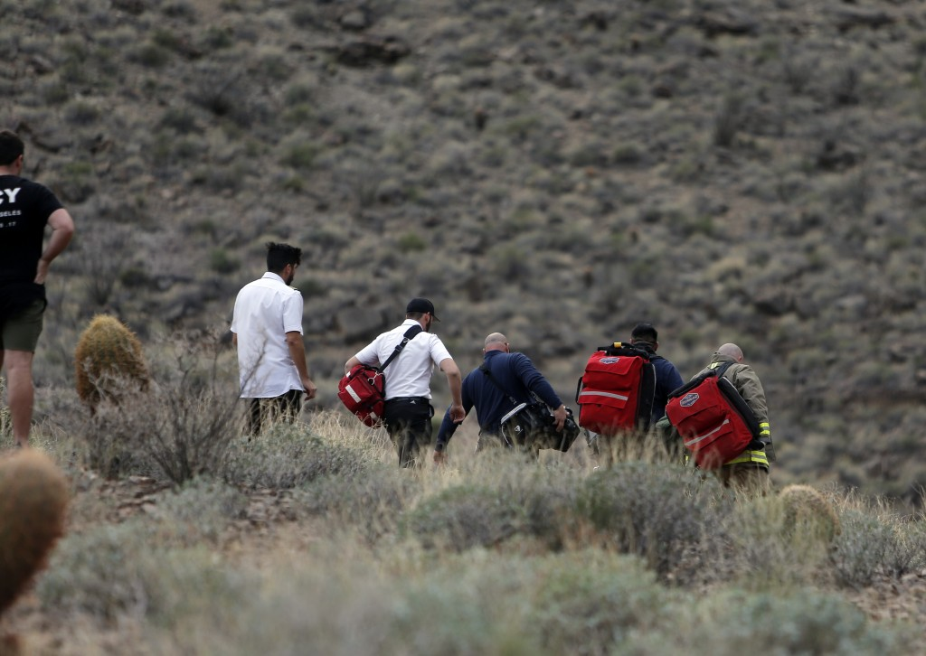 In this Saturday, Feb. 10, 2018, photo, emergency personnel arrive at the scene of a deadly tour helicopter crash along the jagged rocks of the Grand