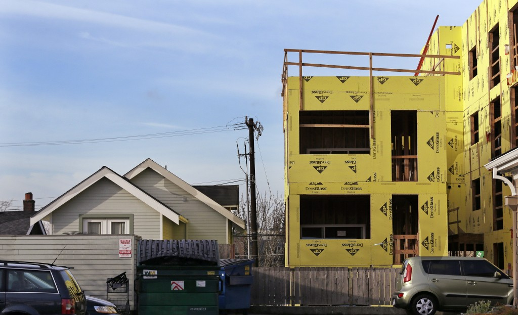 In this Dec. 13, 2017, photo, a four-story mixed-use building is under construction adjacent to an older, single-family home in Seattle. As a solution...