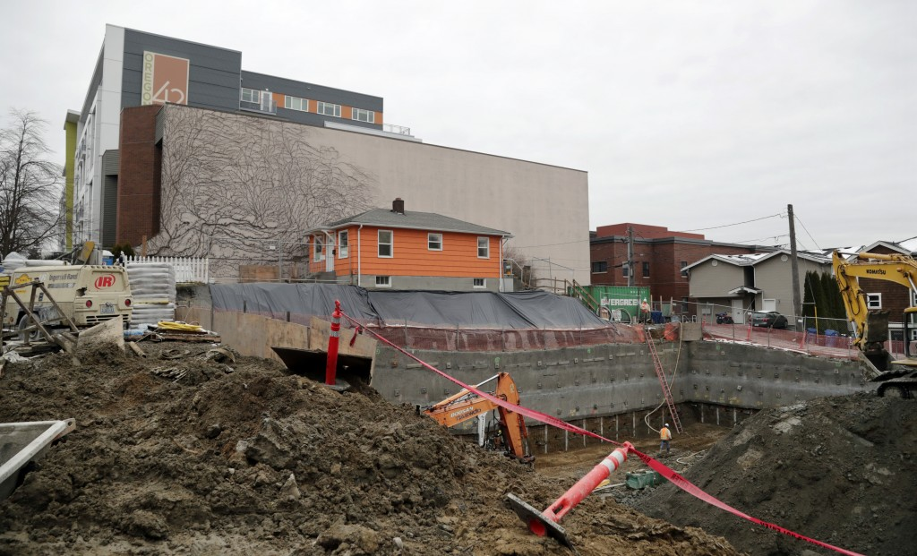 In this Dec. 27, 2017, photo, a single-family home remains on the edge of where a multi-story, mixed-use building is being constructed in Seattle. A m