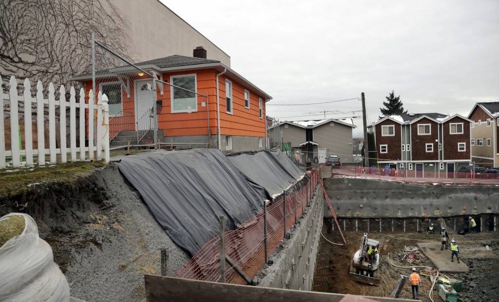 In this Dec. 27, 2017, photo, a single-family home remains on the edge of where a multi-story, mixed-use building is being constructed in Seattle. As ...