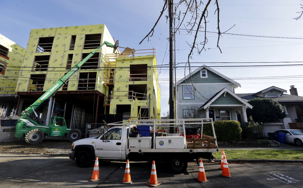 In this Dec. 13, 2017, photo, a four-story mixed-use building is under construction adjacent to an older, single-family home in Seattle. A massive inf...