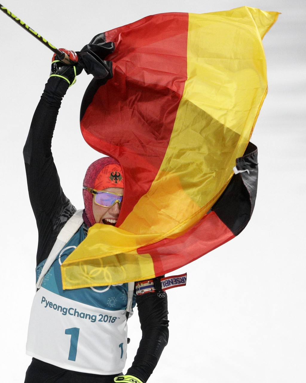 Laura Dahlmeier, of Germany, waves the German flag in the finish area after winning the gold medal in the women's 10-kilometer biathlon pursuit at the