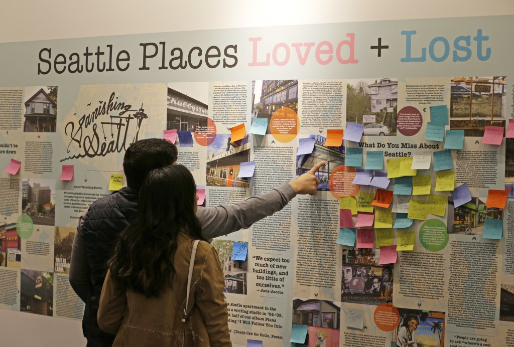 In this Dec. 15, 2017, photo, visitors to the Vanishing Seattle pop-up store in Pike Place Market in Seattle view a display where people are encourage...