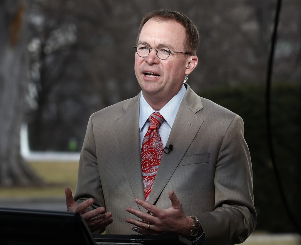 File- This Jan. 22, 2018, file photo shows Director of the Office of Management and Budget Mick Mulvaney talking during a television interview outside