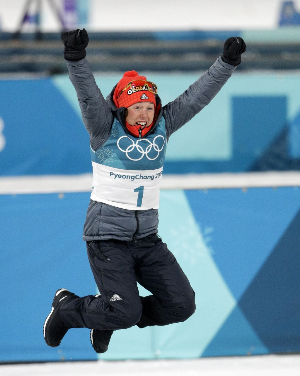Gold medalist Laura Dahlmeier, of Germany, leaps in the air during the venue ceremony at the women's 10-kilometer biathlon pursuit at the 2018 Winter