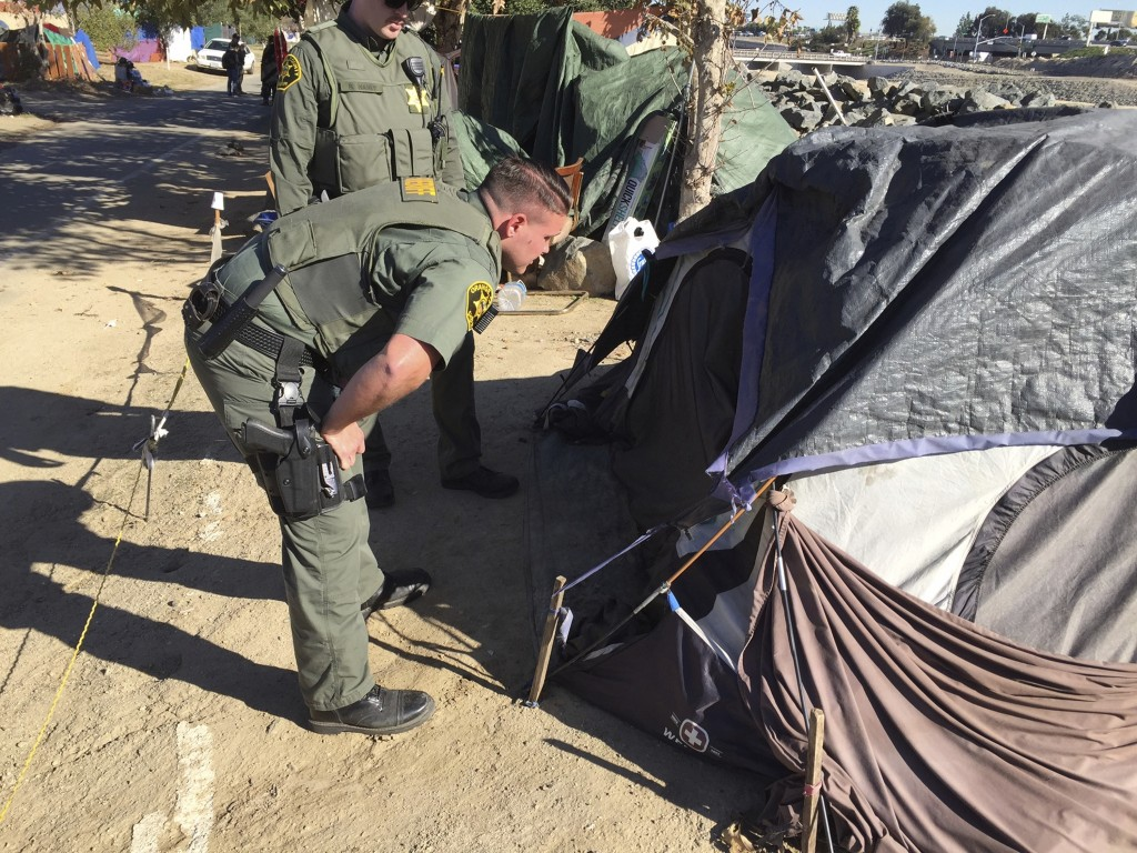 FILE - In this Jan 22, 2018, file photo, Orange County Sheriff's deputies tell people they need to begin he process of packing up along the Santa Ana