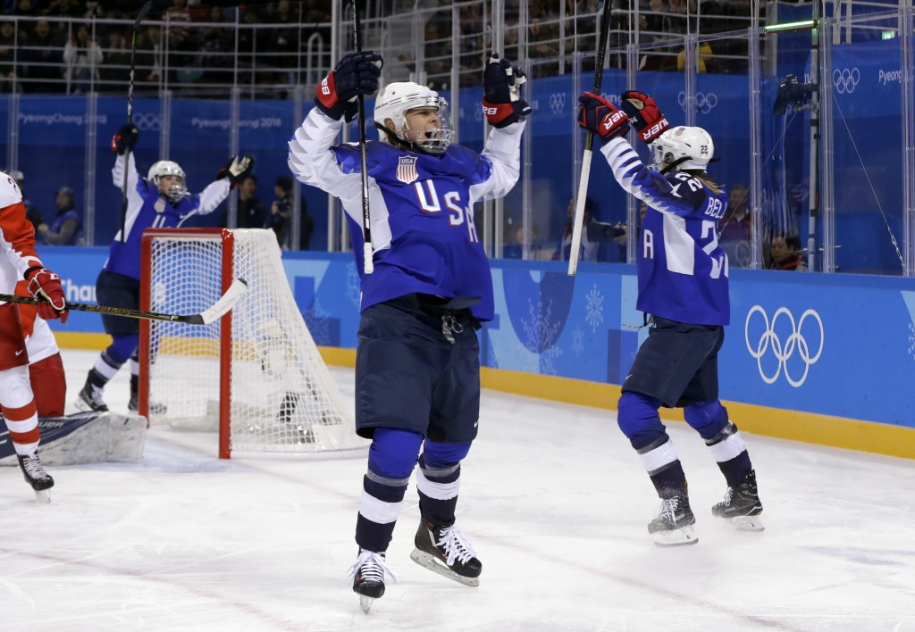 Players from the United States celebrate after Kacey Bellamy scores a goal against the team from Russia during the first period of the preliminary rou