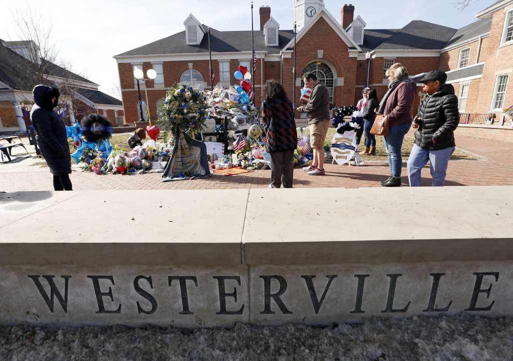 Flowers and signs adorn a Westerville Police car at a memorial outside the police department Monday, Feb. 12, 2018, following a procession transportin