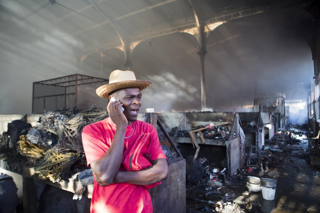 A vendor talks on a phone as he stands in a section of the Iron Market, also known as Marche Hyppolite, in the aftermath of a massive fire, in Port-au