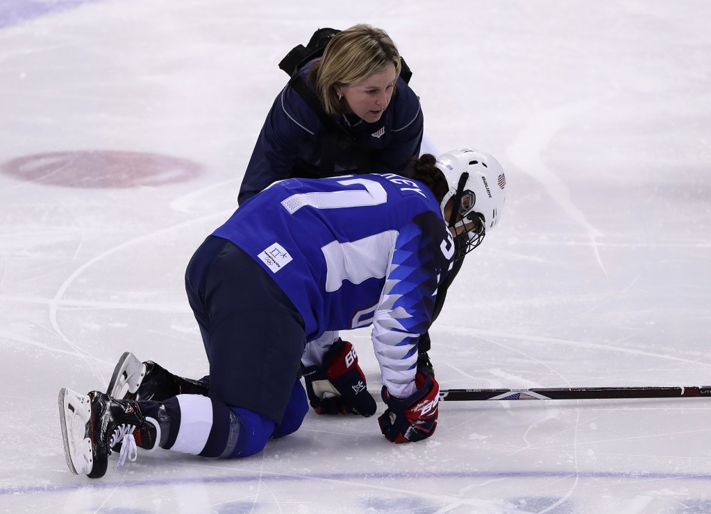Amanda Pelkey, of the United States, is checked by team doctor Ally Howe during the first period of the preliminary round of the women's hockey game a