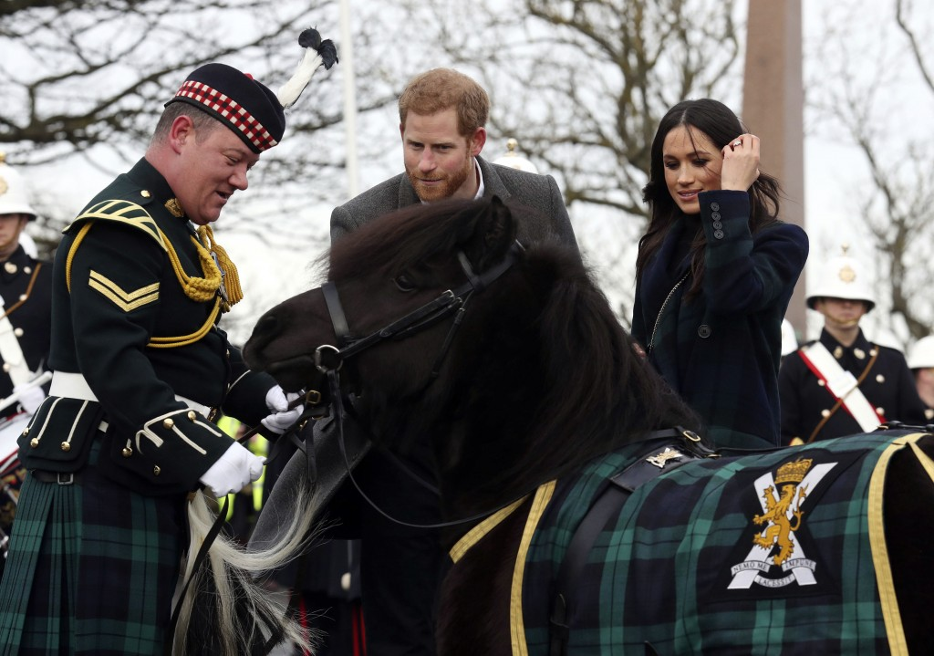 Britain's Prince Harry and Meghan Markle meet Pony Major Mark Wilkinson and regimental mascot Cruachan IV during a walkabout on the esplanade at Edinb