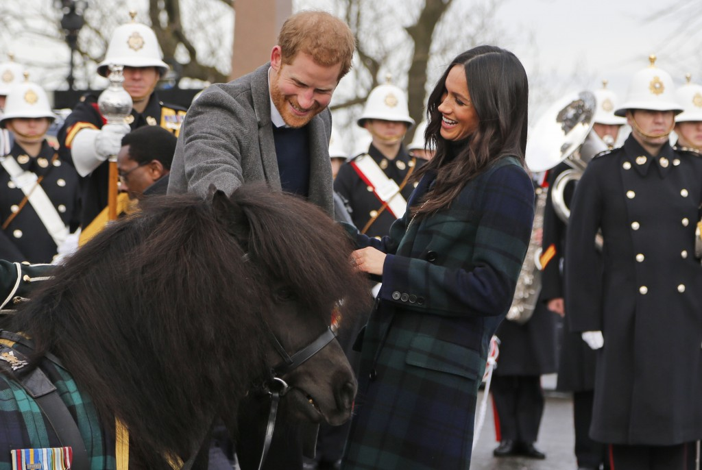 Britain's Prince Harry and his fiancee Meghan Markle meet a Shetland Pony as they arrive at Edinburgh Castle in Edinburgh, Scotland, Tuesday, Feb. 13,