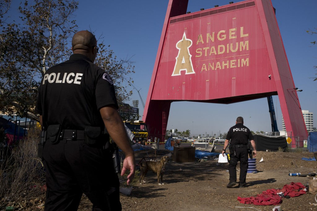 FILE - In this Dec. 19, 2017, file photo, two police officers, Eric Meier, right, and Curtis Bynum from the Anaheim Police Department's homeless outre