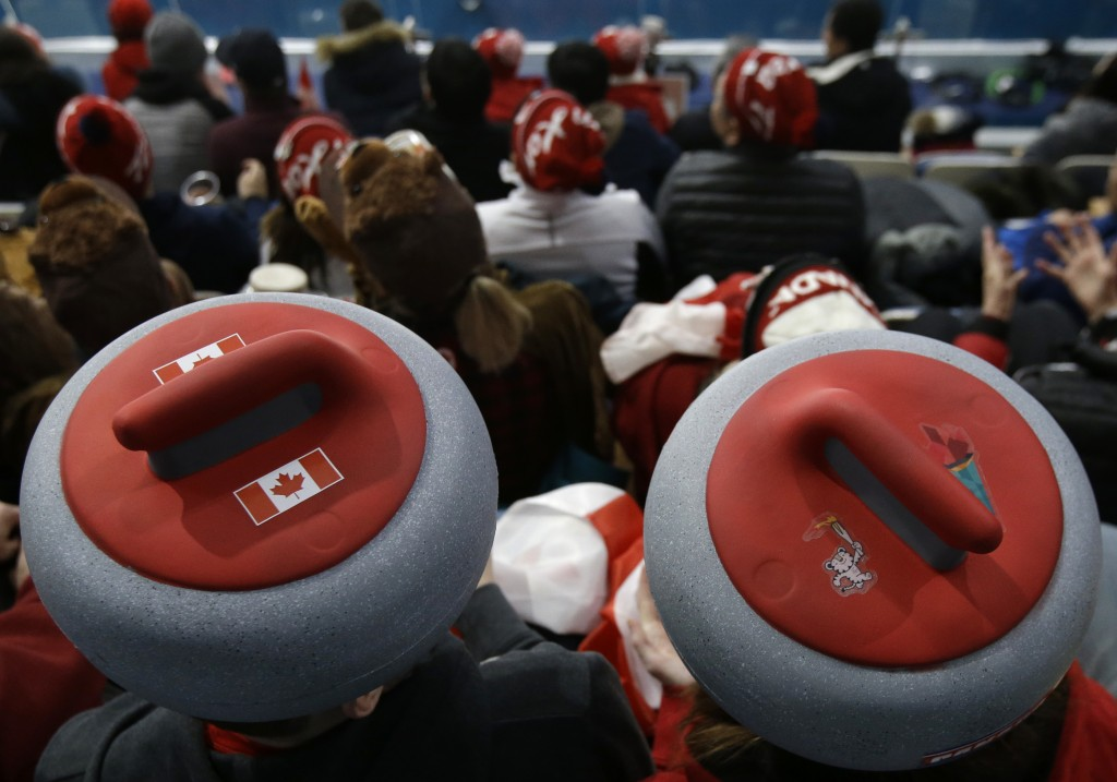 Spectators sport headwear shaped as curling stones as they watch the mixed doubles curling finals match against Canada and Switzerland at the 2018 Win