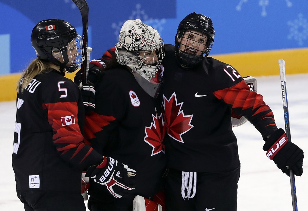 Lauriane Rougeau (5), goalie Shannon Szabados (1) and Meaghan Mikkelson (12), of Canada, celebrate after the preliminary round of the women's hockey g
