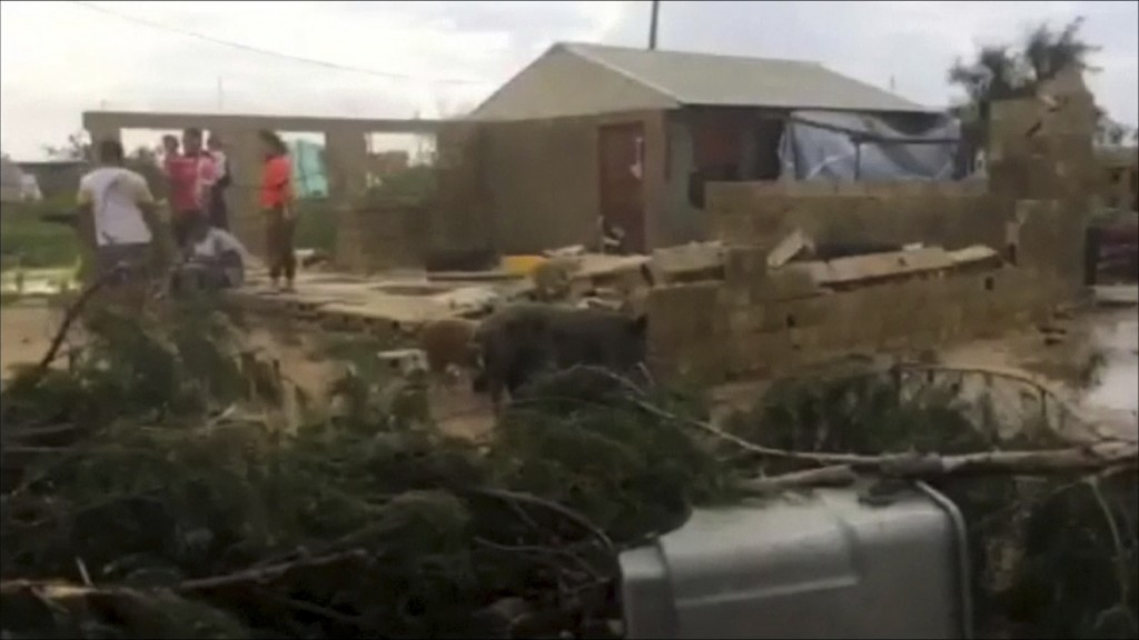 In this image made from a video, people stand near a house damaged by Cyclone Gita in Nuku'alofa, Tonga Tuesday, Feb. 13, 2018. Tonga began cleaning u