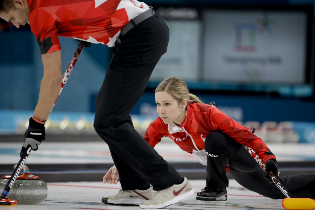 Canada's Kaitlyn Lawes, right, throws a stone as teammate John Morris sweeps the ice during the mixed doubles final curling match against Switzerland