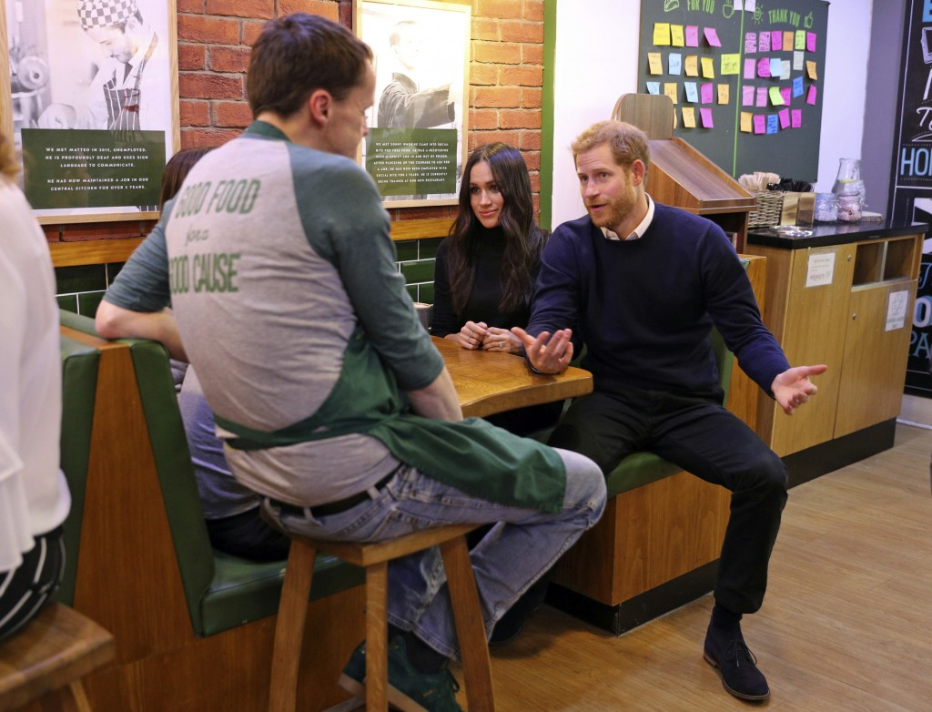 Britain's Prince Harry and Meghan Markle speak with patrons at the Social Bite in Edinburgh, Scotland, Tuesday, Feb. 13, 2018. The recently engaged co