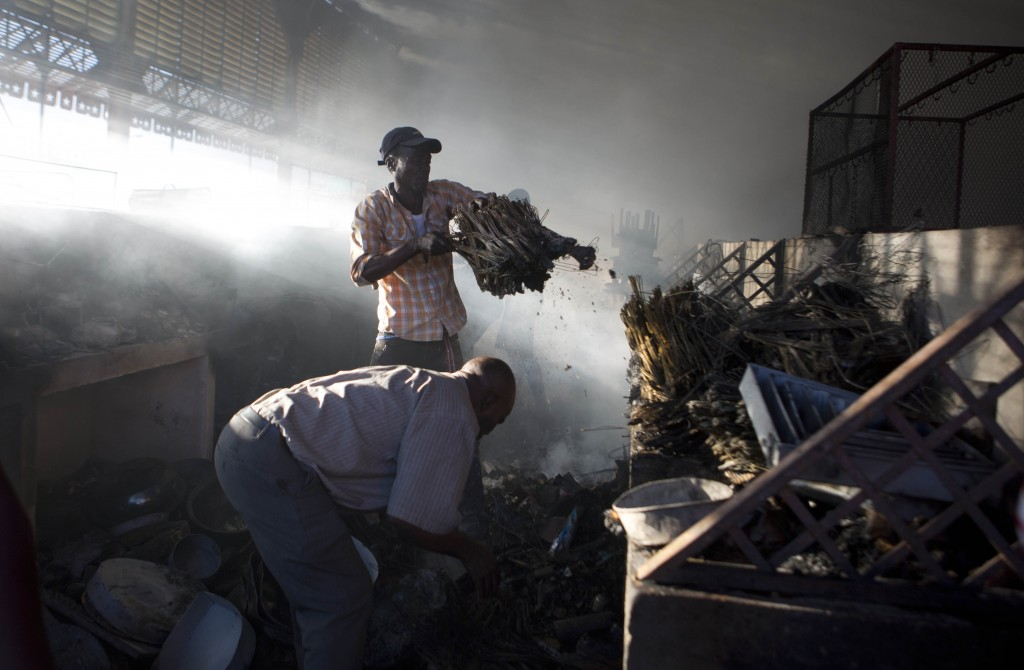 Vendors look for salvageable items in the aftermath of a fire that swept through a section of the Iron Market, also known as Marche Hyppolite, in Port