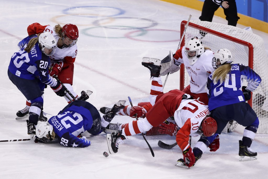 Players collide in front of the goal during the second period of the preliminary round of the women's hockey game between the United States and the te