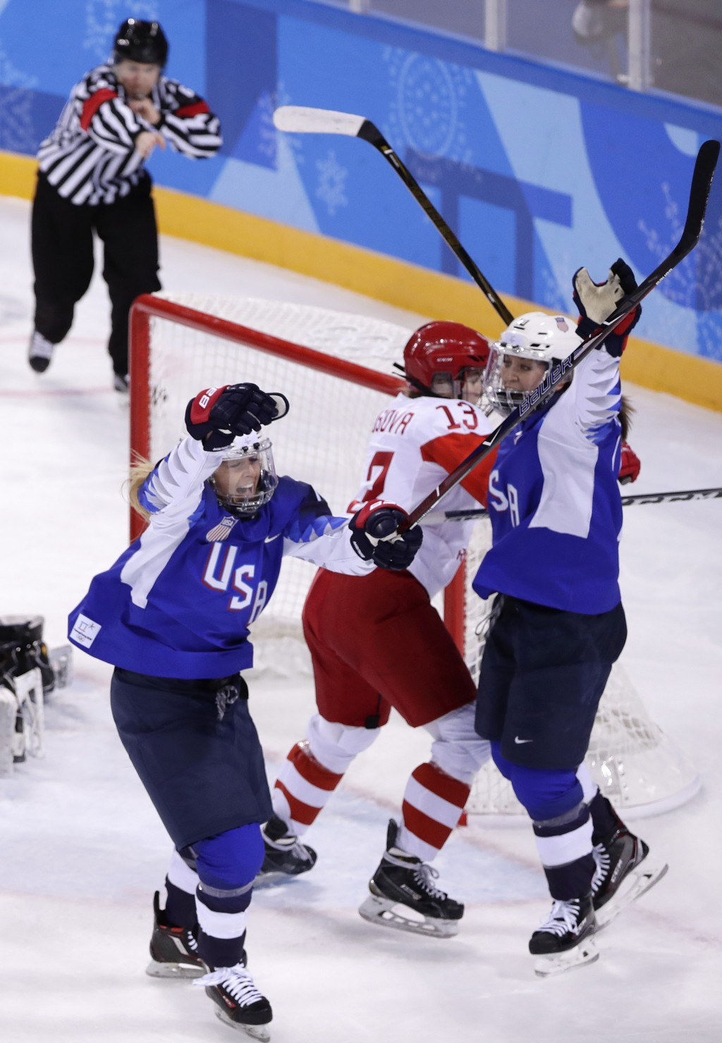 Gigi Marvin, left, of the United States, reacts after scoring a goal during the second period of the preliminary round of the women's hockey game agai