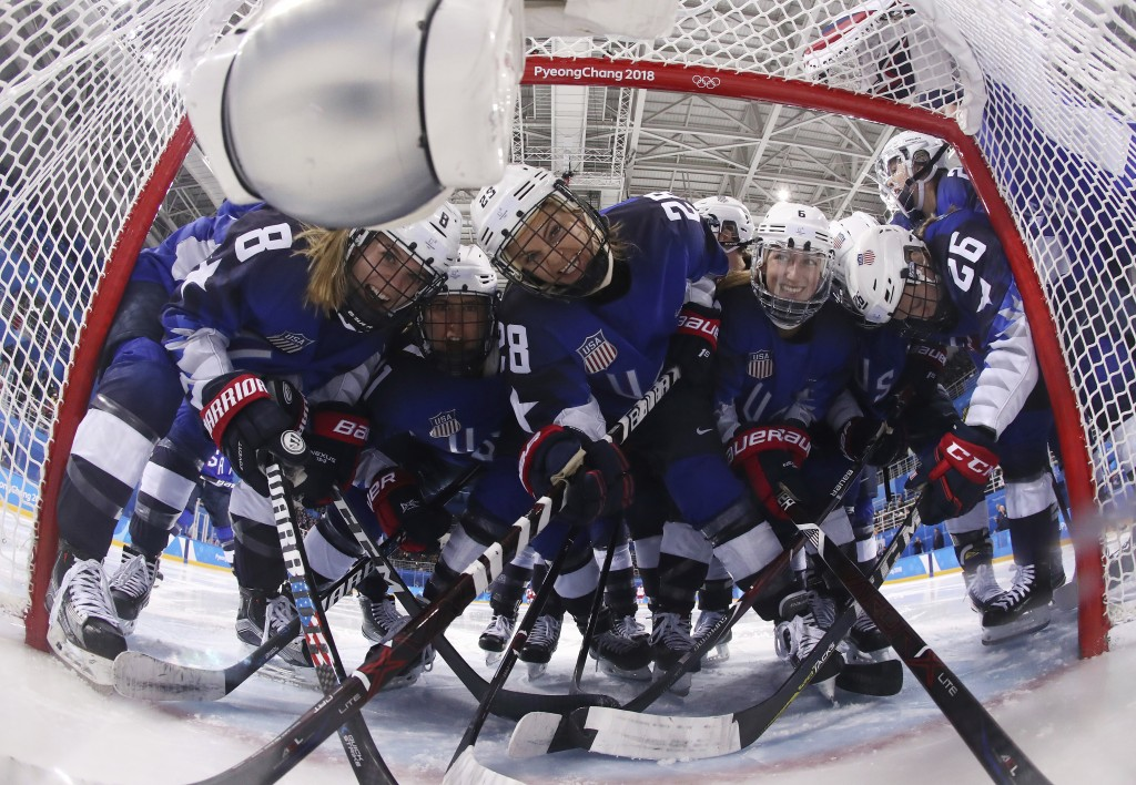 Players from the United States pose for the camera as they gather around the goal before the preliminary round of the women's hockey game against the