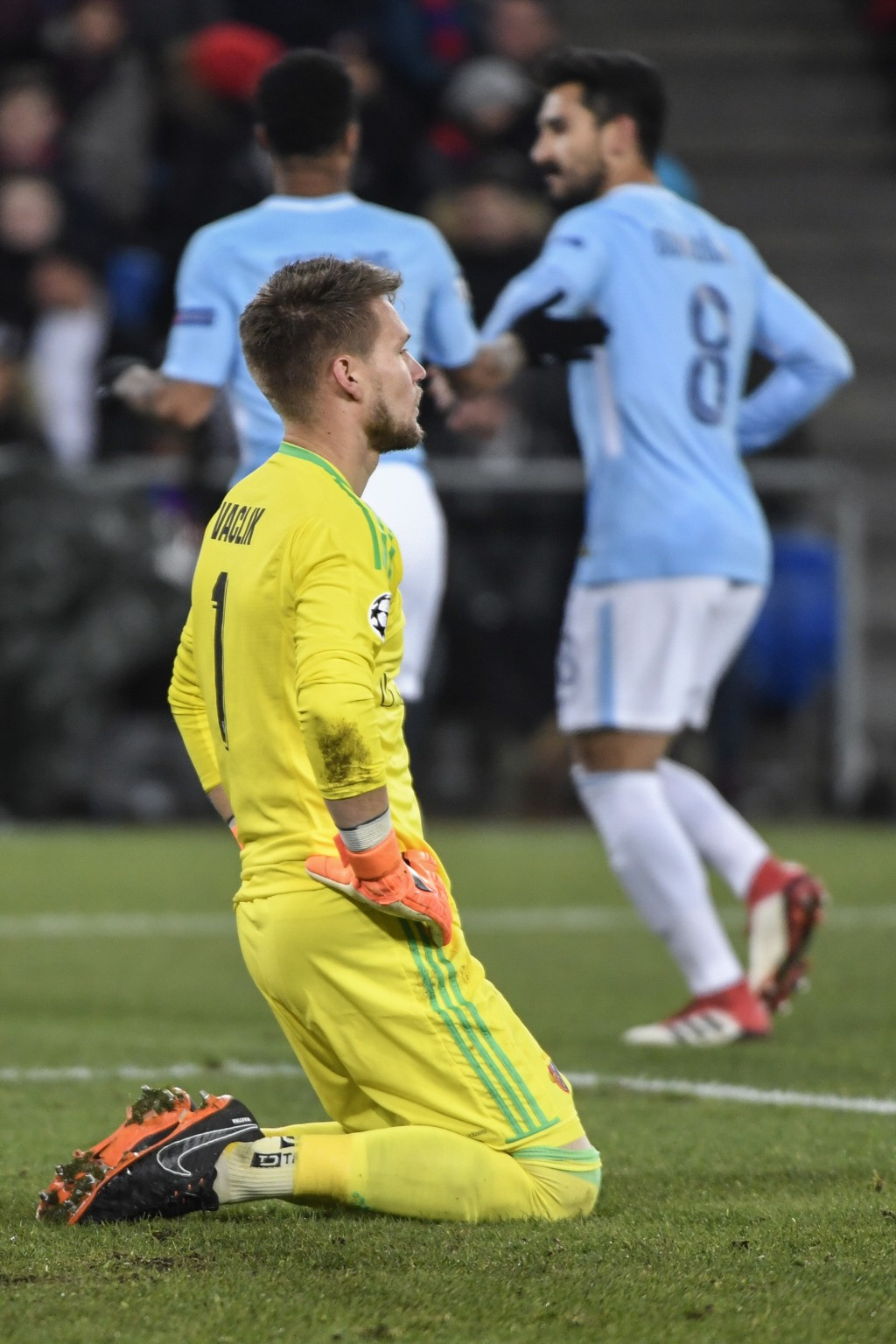 Basel's goalkeeper Tomas Vaclik, front, looks on as Manchester City's Raheem Sterling, left, and Ilkay Gundogan celebrate during the Champions League