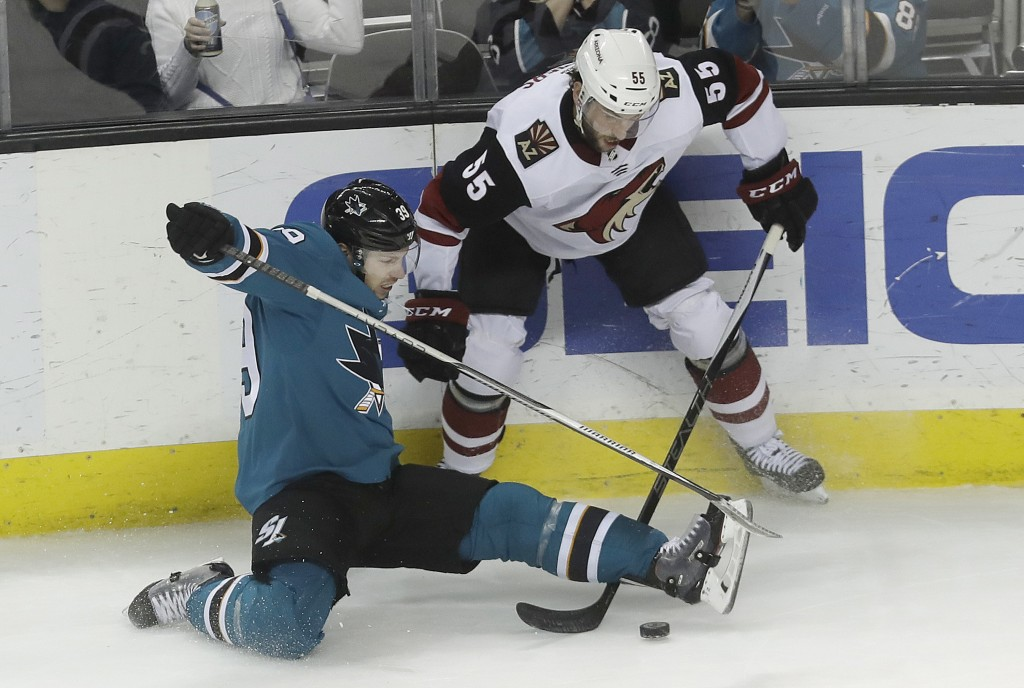 San Jose Sharks center Logan Couture, bottom, falls in front of Arizona Coyotes defenseman Jason Demers (55) during the third period of an NHL hockey