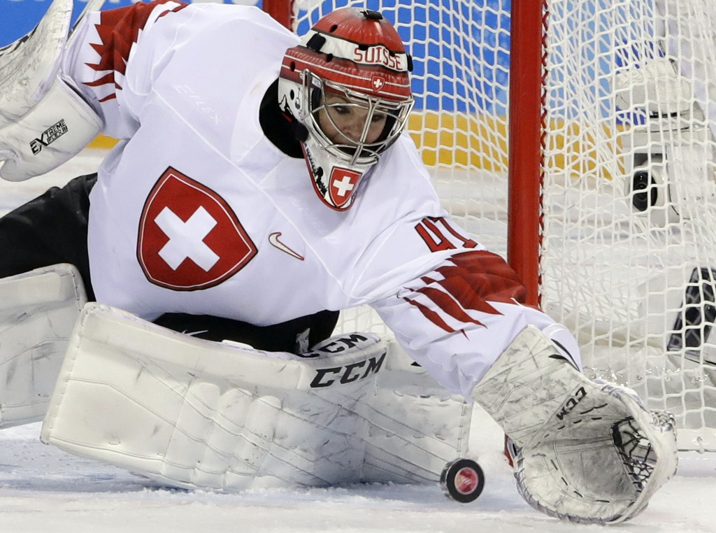 goalie Florence Schelling (41), of Switzerland, reaches for the puck during the third period of the preliminary round of the women's hockey game again