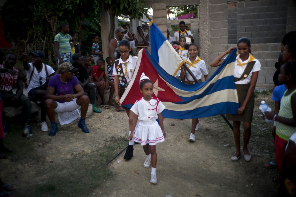 """In this Jan. 22, 2018 photo, girls parade a Cuban flag during the opening ceremony for the week-long student wrestling championship coined """"The truth"""